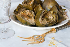 Filled artichokes. Dish of filled artichokes with a gold and silver fork on the front Royalty Free Stock Image