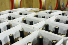 Filled bottles in cardboard boxes in underground wine cellar Stock Images