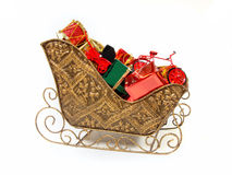 Filled Christmas sleigh. Santa's sleigh filled with colorful gifts and toys on a white background Royalty Free Stock Images