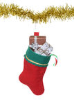 Filled christmas stocking hanging on gold garland Royalty Free Stock Photography