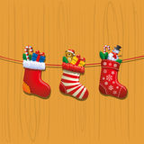 Filled Christmas Stockings. Three Christmas stockings hanging on wood and filled with toys, candy canes and gifts Royalty Free Stock Photos