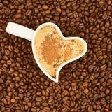 Filled cup on coffee beans Stock Image