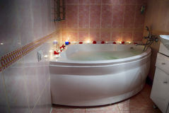 Filled with foam bath, rose petals and candles Stock Photos