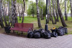 Filled with garbage black plastic bags in nature, in a public Park, along the road, next to the bench. Spring or autumn cleaning royalty free stock photos