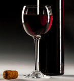 Filled glass of red wine and opened wine bottle Royalty Free Stock Images