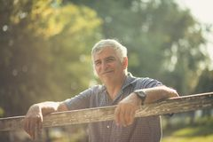 Filled with hope and positivity. Senior man in nature. Copy space. Close up. Looking at camera stock image