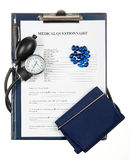 Filled in medical questionnaire with sphygmomanometer Royalty Free Stock Photography