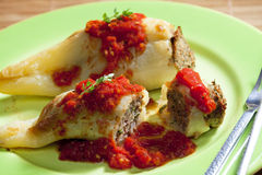 Filled peppers. Peppers filled with smoked meat and celery tops with tomato sauce Stock Images