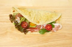 Filled piada flatbread. Piada flatbread filled with salad and parma ham on a wooden chopping board stock photography