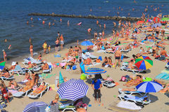 Filled with vacationers people sandy beach on the Baltic Sea