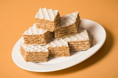 Filled wafer cake dessert. On white plate on orange background stock photo