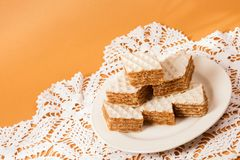 Filled wafer cake dessert. Filled wafer cake sweet dessert is on plate on orange background stock images