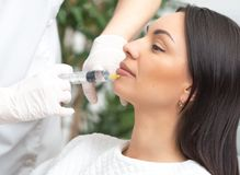 Filler injection for face. Plastic aesthetic facial surgery. Doctor woman giving injections with syringe injects lips and botox. Filler injection for face stock photos