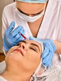 Dermal fillers lips of woman in spa salon with beautician. Filler injection female face. Plastic aesthetic facial surgery in beauty clinic. Elderly women 50-60 stock images