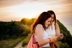 Filles à l'aide d'un smartphone au coucher du soleil Photographie stock libre de droits