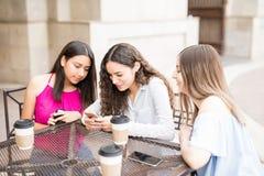 Filles à l'aide du téléphone portable au restaurant Image stock