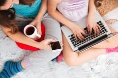 Filles à l'aide du téléphone portable d'ordinateur portable et d'écran vide à la maison Image libre de droits