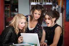 Filles étonnées regardant un ordinateur portatif Photographie stock libre de droits