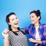 Filles adolescentes d'école de meilleurs amis ayant ensemble l'amusement, posant sur le fond bleu, sourire heureux de besties, mo Image stock