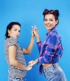 Filles adolescentes d'école de meilleurs amis ayant ensemble l'amusement, pose émotive sur le fond bleu, sourire heureux de besti Photo stock