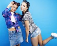 Filles adolescentes d'école de meilleurs amis ayant ensemble l'amusement, pose émotive sur le fond bleu, sourire heureux de besti Photographie stock libre de droits