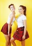 Filles adolescentes d'école de meilleurs amis ayant ensemble l'amusement, pose émotive sur le fond jaune, sourire heureux de best Image libre de droits