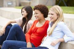 Filles adolescentes d'étudiant s'asseyant dehors Image stock