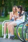 Filles adolescentes gaies de cycliste à l'aide du téléphone mobile Image libre de droits