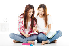 filles adolescentes heureuses d'étudiants observant les livres Photo libre de droits