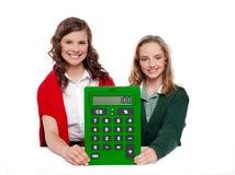 Filles affichant la grande calculatrice verte à l'appareil-photo Photographie stock