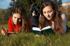 Filles affichant les livres sur la pelouse Image stock