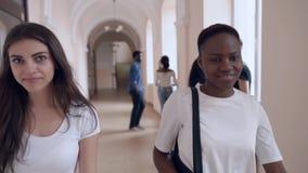Filles africaines et caucasiennes disant le bye aux amis dans l'université banque de vidéos