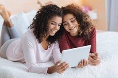 Filles amicales avec la tablette appréciant le temps libre ensemble Photographie stock libre de droits