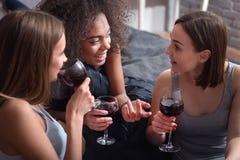 Filles amusées buvant du vin et ayant la conversation passionnante Images libres de droits