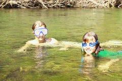 Filles appréciant l'eau de rivière Images libres de droits