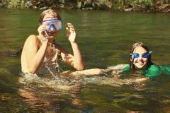 Filles appréciant l'eau de rivière Images stock