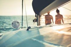 Filles appréciant le coucher du soleil sur la mer et le yacht Fond abstrait de navigation photographie stock