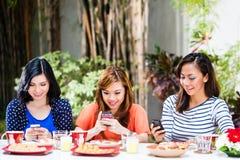Filles asiatiques à l'aide de leurs téléphones portables Image stock