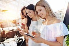 Filles attentives regardant vers le bas leurs téléphones Image stock