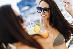 Filles attirantes buvant des cocktails sur la plage Photographie stock libre de droits