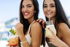 Filles attirantes buvant des cocktails sur la plage Images libres de droits