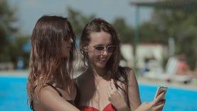 Filles attirantes dans les lunettes de soleil et le bikini faisant a banque de vidéos
