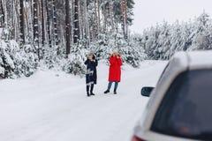 Filles au milieu de la route parlant au téléphone en la voiture sur a images libres de droits