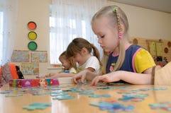 Filles aux puzzles de jeu de table Images stock