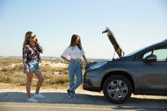 Filles avec cassées une voiture sur la route de campagne Image libre de droits