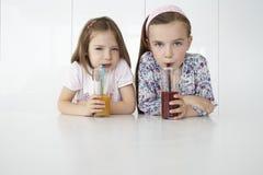 Filles avec des boissons d'orange et de chocolat au Tableau Photographie stock