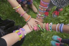 Filles avec des bracelets de métier à tisser remontant leurs mains images libres de droits