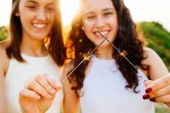 Filles avec des cierges magiques au coucher du soleil Image libre de droits