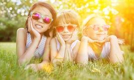 Filles avec des lunettes de soleil au pré en été Photos stock