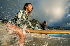 Filles avec des planches de surf en éclaboussant la vague sur une plage Image stock
